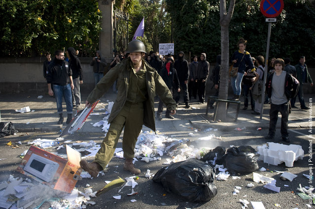 A student dressed up as a soldier throws garbage on the street during a demonstration on February 29, 2012 in Barcelona