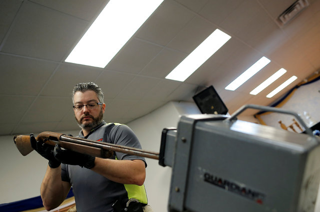 "A Chicago Police officer examines a shotgun turned in from the public as part of the ""Gun Turn-in"" event where a gift card is given for every firearm turned over to police at Universal Missionary Baptist Church in Chicago, Illinois, U.S. May 28, 2016. (Photo by Jim Young/Reuters)"