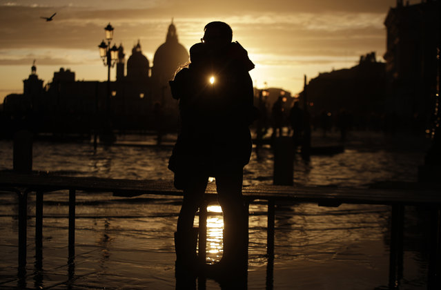 A couple stands in a golden sunset in Venice on Sunday, November 17, 2019 just hours after an exceptional 1.5 meter tide receded from nearby St. Mark's Square. It was the third flood topping 1.5 meters this week, following Tuesday's 1.87-meter flood which was the worst in 53 years. (Photo by Luca Bruno/AP Photo)