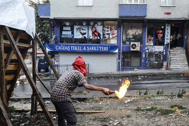 A protester hurls a petrol bomb towards a police car in Istanbul, Friday, July 24, 2015, during clashes between police and protesters denouncing the deaths of 32 people at an suicide bombing Monday in Suruc, southeastern Turkey. Turkish warplanes struck Islamic State group targets across the border in Syria early Friday, in a strong tactical shift for Turkey which had long been reluctant to join the U.S.-led coalition against the extremist group. (Photo by Cagdas Erdogan/AP Photo/Depo Photos)