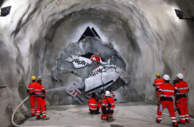 """In this June 16, 2009 file photo minors watch the tunnel drilling machine """"Gabi"""" breaking through the last section of the AlpTransit """"New Railway Link through the Alps"""" (NRLA) tunnel between Erstfeld and Amsteg, Switzerland. The celebrations of the opening of the Gotthard  Base Tunnel  will start on June 1, 2016. (Photo by Sigi Tischler/Keystone via AP Photo)"""