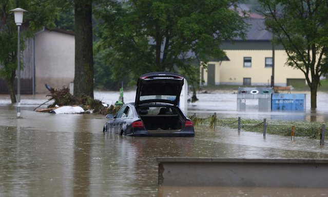 A car stands in the water in the flooded street in the Bavarian village of Triftern east of Munich, Germany, June 1, 2016. (Photo by Michaela Rehle/Reuters)