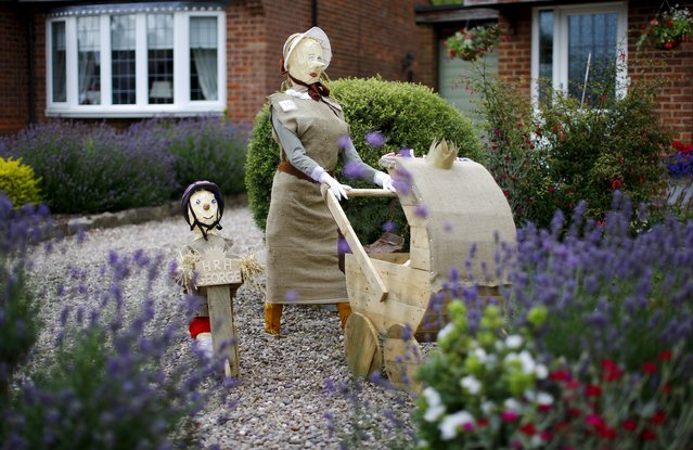 A scarecrow of Britain's Prince George and Princess Charlotte with their nanny stands in a garden during the Scarecrow Festival in Heather, Britain, July 28, 2015. The annual event asks residents of Heather to make scarecrow's to raise thousands of pounds for local groups and charities. (Photo by Darren Staples/Reuters)