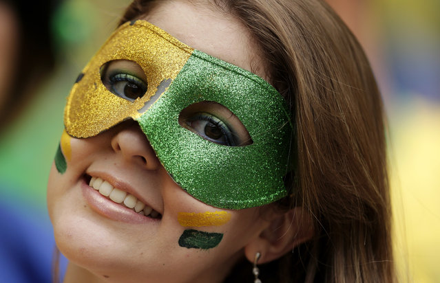 A Brazilian fan poses with her mask before the group A World Cup soccer match between Brazil and Mexico at the Arena Castelao in Fortaleza, Brazil, Tuesday, June 17, 2014. (Photo by Marcio Jose Sanchez/AP Photo)