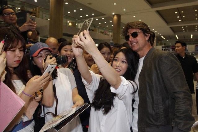 "Tom Cruise poses with fans as he arrives in support of the ""Mission: Impossible – Rogue Nation"" World Press Tour at Incheon International Airport on July 30, 2015 in Incheon, South Korea. (Photo by Chung Sung-Jun/Getty Images  for Paramount Pictures International)"