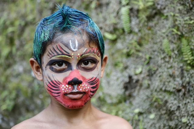 A boy with a painted face poses during the Grebeg Ritual on June 25, 2014 in Tegallalang Village, Gianyar, Bali, Indonesia. During the biannual ritual, young members of the community parade through the village with painted faces and bodies to ward off evil spirits. (Photo by Putu Sayoga/Getty Images)