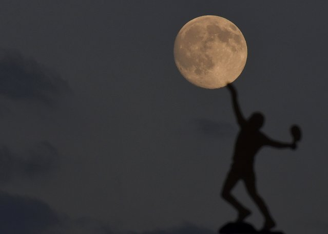 The moon rises above the weather vane at the All England Lawn Tennis and Croquet Club which hosts the Wimbledon Tennis Championships in London, June 30, 2015. (Photo by Toby Melville/Reuters)