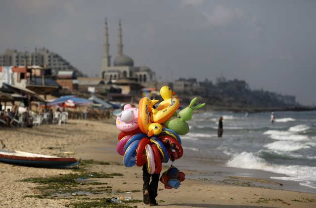 A Palestinian vendor walks along a beach in Gaza City selling inflatable toys on July 27, 2015. (Photo by Mohammed Abed/AFP Photo)