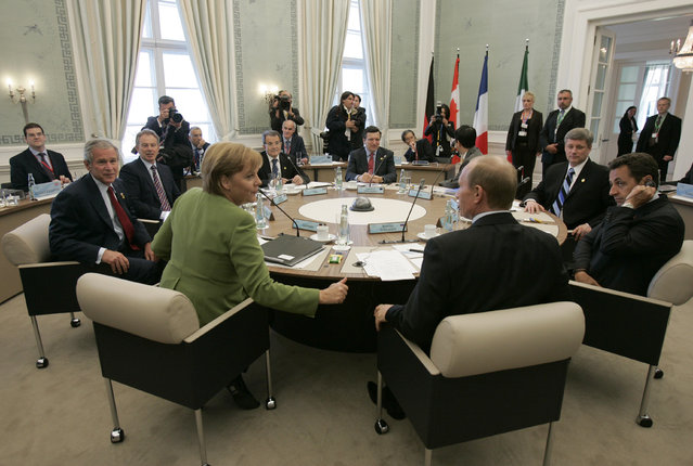 German Chancellor Angela Merkel, U.S. President George W. Bush (obscured), British Prime Minister Tony Blair, Italian Prime Minister Romano Prodi, European Commission President Jose Manuel Barroso, Japanese Prime Minister Shinzo Abe (obscured), Canadian Prime Minister Stephen Harper, French President Nicolas Sarkozy and Russian President Vladimir Putin (clockwise from L) are seen during a working meeting in Heiligendamm June 7, 2007. Leaders from the world's major industrialised nations meet in the Baltic resort of Heiligendamm on June 6-8 for a Group of Eight (G8) summit. (Photo by Denis Sinyakov/AP Photo)