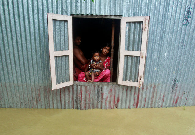 A woman and a child look out from a window of their house at a flooded village on the outskirts of Agartala, India, June 19, 2017. (Photo by Jayanta Dey/Reuters)
