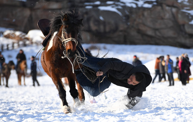 A residents performs equestrian skill at the second Sawur cultural tourism festival on animal husbandry in winter in Jeminay County, northwest China's Xinjiang Uygur Autonomous Region, December 29, 2019. (Photo by Song Yanhua/Xinhua News Agency/Barcroft Media)