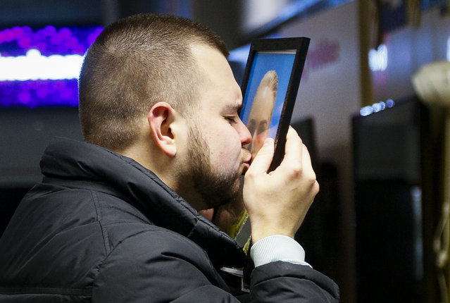 The partner of Julia Sologub, a member of the flight crew of the Ukrainian 737-800 plane that crashed on the outskirts of Tehran, kisses a portrait of her at a memorial inside Borispil international airport outside Kyiv, Ukraine, Wednesday, January 8, 2020. A Ukrainian airplane carrying 176 people crashed on Wednesday shortly after takeoff from Tehran's main airport, killing all onboard, Iranian state TV and officials in Ukraine said. (Photo by Efrem Lukatsky/AP Photo)