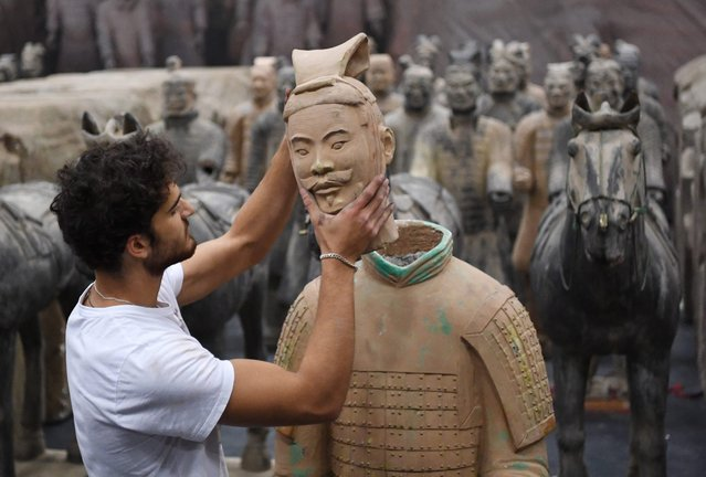 """A picture made available on 17 June 2016 shows a helper placing a head on a terracotta warrior in the exhibition """"The Terracotta Army & The Legacy of the Eternal Emperor"""", which shows, among other artworks, replicas of the terracotta soldiers of the first Chinese emperor, in Ludwigsburg, Germany, 16 June 2016. The exhibition runs from 22 June to 11 September 2016. (Photo by Marijan Murat/EPA)"""