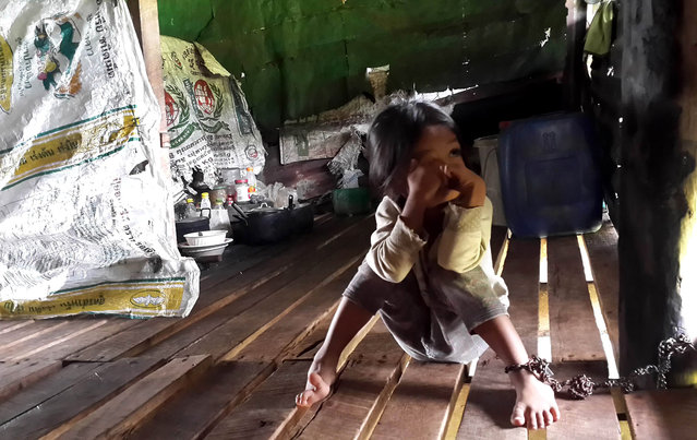 This handout photo taken on July 4, 2014 and released by the Cambodian Human Rights and Development Association (ADHOC) on July 7, 2014 shows a Cambodian girl sittign with her leg chained to a pillar in her home in Koh Kong province. A four-year-old girl, who have been chained up to eight hours a day for nearly two years by her adopted mother, was rescued, Cambodian police and a rights activist said on July 7, 2014. (Photo by AFP Photo/ADHOC)
