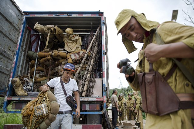 """Actors get dressed into Japanese Army World War Two costumes minutes after playing small roles as Chinese soldiers on the set of """"The Last Prince"""" television series on location near Hengdian World Studios near Hengdian July 24, 2015. (Photo by Damir Sagolj/Reuters)"""