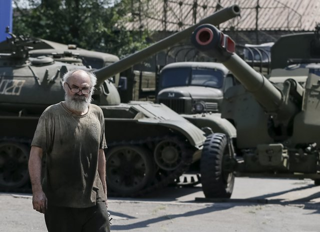 A worker passes by an old soviet tank and cannon at a Phaeton museum in Zaporizhia, Ukraine, August 11, 2015. (Photo by Gleb Garanich/Reuters)