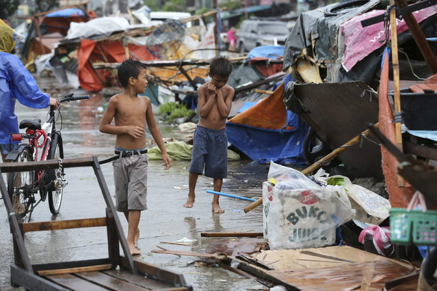 Young residents look at the remains of damaged homes as Typhoon Rammasun batters suburban Navotas, north of Manila, Philippines on Wednesday, July 16, 2014. Typhoon Rammasun knocked out power in many areas but it spared the Philippine capital, Manila, and densely-populated northern provinces from being directly battered Wednesday when its fierce wind shifted slightly away, officials said. (Photo by Aaron Favila/AP Photo)