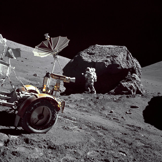 "Geologist-Astronaut Harrison H. Schmitt is photographed standing next to a huge, split boulder at Station 6 on the sloping base of North Massif during the third Apollo 17 extravehicular activity (EVA-3) at the Taurus-Littrow landing site. The ""Rover"" Lunar Roving Vehicle (LRV) is in the left foreground. Schmitt is the Apollo 17 Lunar Module pilot. This picture was taken by Commander Eugene A. Cernan. (Photo by NASA)"