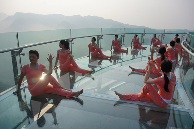 People practise yoga on a glass sightseeing platform ahead of the International Day of Yoga, on the outskirts of Beijing, China, June 20, 2016. (Photo by Reuters/Stringer)