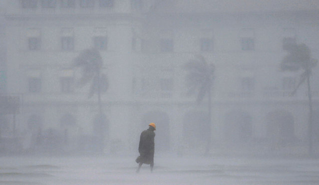 A man walks in heavy rain during a wet day in Colombo, Sri Lanka on September 24, 2019. (Photo by Dinuka Liyanawatte/Reuters)