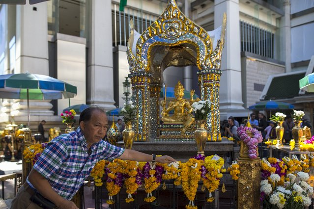 A man places a garland at the Erawan shrine, the site of Monday's deadly blast, in central Bangkok, Thailand, August 19, 2015. The government said Monday evening's attack at the popular Erawan shrine in the heart of Bangkok was aimed at wrecking the economy, which depends heavily on tourism. No one has claimed responsibility for the blast, which killed 22 – nearly half of them foreigners – and wounded more than 120. (Photo by Athit Perawongmetha/Reuters)
