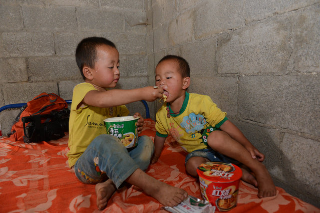 A child feeds his companion with instant noodles after they were evacuated from the site of a landslide in Bijie, Guizhou province, China, July 1, 2016. (Photo by Reuters/Stringer)