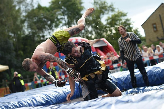 Competitors take part in the 10 th annual World Gravy Wrestling Championships held at the Rose 'n' Bowl Pub near Bacup, north west England on August 28, 2017. Contestants participate in fancy dress and wrestle in a pool of Lancashire Gravy for two minutes whilst being scored for a variety of wrestling moves. (Photo by Oli Scarff/AFP Photo)