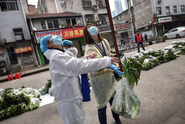 A resident (unseen) uses a belt to get vegetables in Wuhan, in China's central Hubei province on March 13, 2020. China reported just eight cases of the coronavirus on March 13, with no new domestic infections outside the epicentre of Hubei province. (Photo by AFP Photo/China Stringer Network)