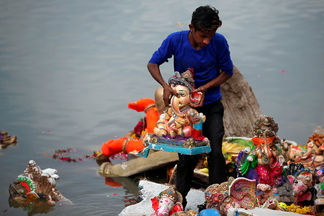 A man holds an idol of the Hindu god Ganesh, the deity of prosperity, after it was immersed in the waters of the Sabarmati river during the ten-day long Ganesh Chaturthi festival in Ahmedabad, August 30, 2017. (Photo by Amit Dave/Reuters)