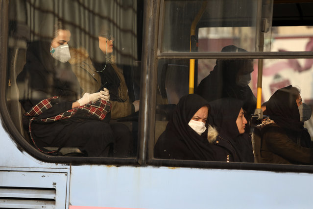 """Woman, wearing face masks, travel on a public bus in a street in western Tehran, Iran, Saturday, February 29, 2020. Iran is preparing for the possibility of """"tens of thousands"""" of people getting tested for the new coronavirus as the number of confirmed cases spiked again Saturday, Health Ministry spokesman Kianoush Jahanpour said, underscoring the fear both at home and abroad over the outbreak in the Islamic Republic. (Photo by Vahid Salemi/AP Photo)"""