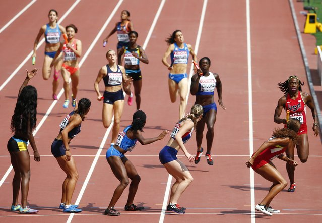 Athletes pass the baton during their women's 4 x 400 metres relay heat at the 15th IAAF Championships at the National Stadium in Beijing, China August 29, 2015. (Photo by David Gray/Reuters)