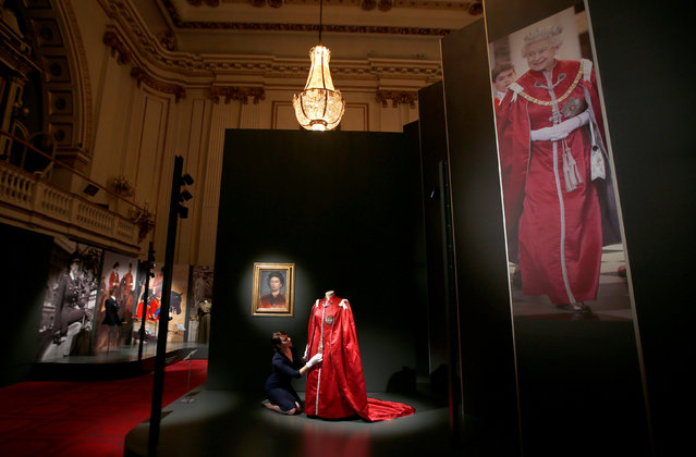 """A member of the Royal Collection Trust, poses for photographers next to Britain's Queen Elizabeth's """"Mantle of The Order of The British Empire"""" robe, ahead of the opening of an exhibition entitled '""""ashioning a Reign: 90 Years of Style from the Queen's Wardrobe"""", at Buckingham Palace, in London, Britain July 21, 2016. (Photo by Peter Nicholls/Reuters)"""