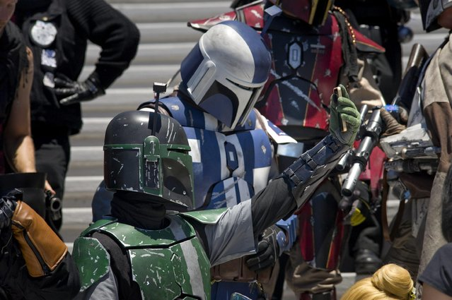 A cosplayer (L, bottom) dressed as a Star Wars fictional character Boba Fett takes a selfie as he prepares for a group photo outside Comic Con 2016 in San Diego, California, USA, 22 July 2016. (Photo by David Maung/EPA)