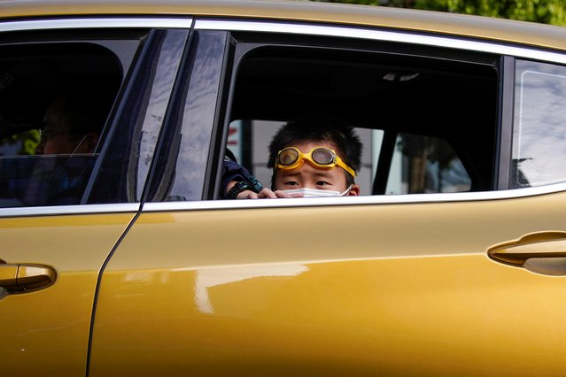 A boy wearing a face mask is seen inside a car after the lockdown was lifted in Wuhan, capital of Hubei province and China's epicentre of the novel coronavirus disease (COVID-19) outbreak, April 14, 2020. (Photo by Aly Song/Reuters)
