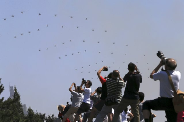 People take pictures as military helicopters fly across the sky during the military parade marking the 70th anniversary of the end of World War Two, in Beijing, China, September 3, 2015. (Photo by Reuters/Stringer)