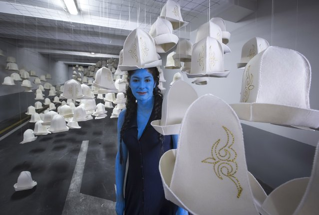 Sarah Trouche, a French visual performer, poses at an installation called Kyrgyz Pass, made of national felt hats, by artist Syrlybek Bekbotayev during the contemporary art Artbat festival in Almaty August 30, 2014. (Photo by Shamil Zhumatov/Reuters)