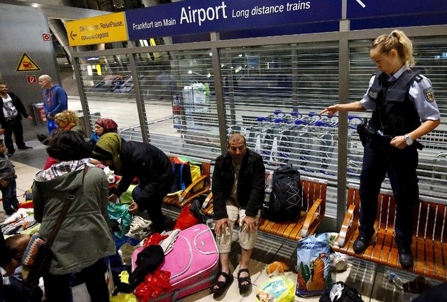 A German border policewoman stands on a bench while talking to migrants who unexpectedly disembarked a train that departed from Budapest's Keleti station, at the railway station of the airport in Frankfurt, Germany, early morning September 6, 2015. (Photo by Kai Pfaffenbach/Reuters)