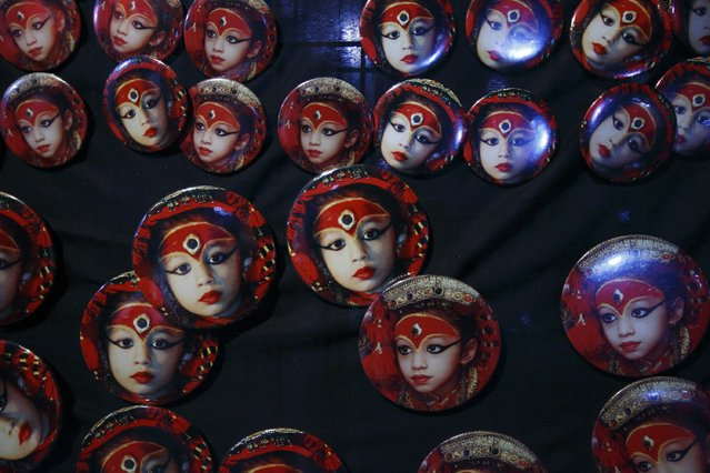 Badges with portraits of the living goddess Kumari are seen on sale along a street during the Indra Jatra festival in Kathmandu September 8, 2014. The annual festival, named after Indra, the god of rain and heaven, is celebrated by worshipping, rejoicing, singing, dancing and feasting in Kathmandu Valley to mark the end of monsoon season. Indra, the living goddess Kumari and other deities are worshipped during the festival. (Photo by Navesh Chitrakar/Reuters)
