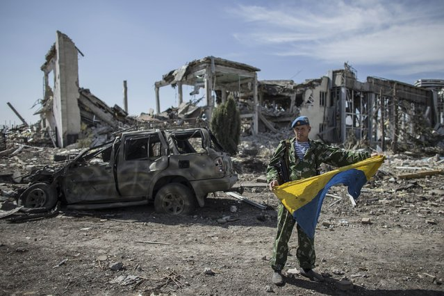 A pro-Russian rebel displays a captured Ukrainian flag at the destroyed airport in Luhanks, eastern Ukraine, September 14, 2014. (Photo by Marko Djurica/Reuters)