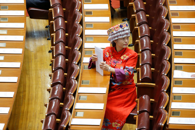 A delegate wearing traditional costume prepares for the opening session of the 19th National Congress of the Communist Party of China at the Great Hall of the People in Beijing, China on October 18, 2017. (Photo by Thomas Peter/Reuters)