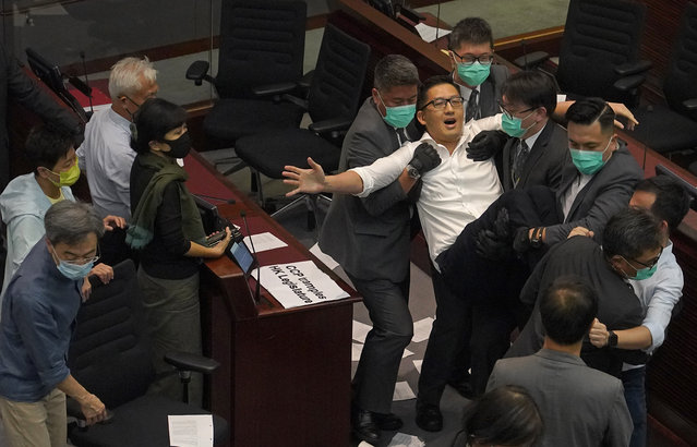 Pan-democratic politician Lam Cheuk-ting is taken away by security guards after Lam throws papers to pro-Beijing politician Chan Kin-por as they attend a Legislative Council's House Committee meeting in Hong Kong, Monday, May 18, 2020. Scuffles broke out in Hong Kong's legislature for a second time this month, with security guards ejecting several pro-democracy lawmakers as the city's pro-democracy and pro-Beijing camps continue to wrestle for control over a key committee that scrutinizes bills. (Photo by Vincent Yu/AP Photo)