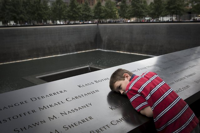 A child lays on the memorial during a ceremony marking the 14th anniversary of the attacks on the World Trade Center at The National September 11 Memorial and Museum in Lower Manhattan in New York, September 11, 2015. (Photo by Andrew Kelly/Reuters)