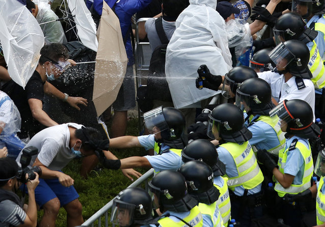 Riot police use pepper spray as they clash with protesters, as tens of thousands of protesters block the main street to the financial Central district outside the government headquarters in Hong Kong September 28, 2014. (Photo by Bobby Yip/Reuters)