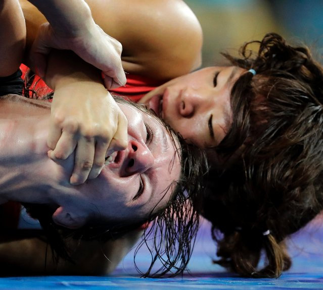 Latvia's Anastasija Grigorjeva, left, and Japan's Risako Kawai compete during the women's wrestling freestyle 63-kg competition at the 2016 Summer Olympics in Rio de Janeiro, Brazil, August 18, 2016. (Photo by Charlie Riedel/AP Photo)