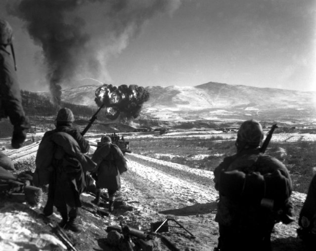 U.S. Marines move forward after effective close-air support flushes out the enemy from their hillside entrenchments.  Billows of smoke rise skyward from the target area.  Hagaru-ri. December 26, 1950. (Photo by Cpl. McDonald, Marine Corps)