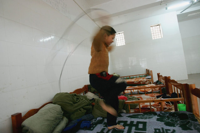 A kid skips on his bed at an assistance center February 23, 2005 in Shenzhen, Guangdong Province, China. (Photo by Cancan Chu/Getty Images)