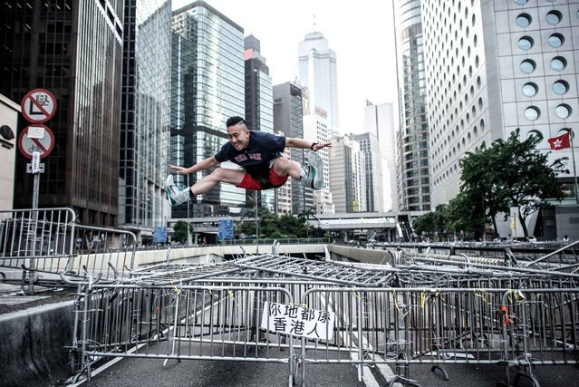 A man jumps from a barricade of pro-democracy demonstrators in Hong Kong on October 6, 2014. Exhausted Hong Kong demonstrators debated the next step in their pro-democracy campaign as their numbers dwindled after a week of rallies, and the city returned to work despite road closures and traffic gridlock. (Photo by Philippe Lopez/AFP Photo)