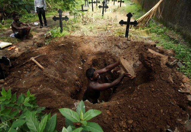 A gravedigger empties out mud as he digs a grave for the burial of a person who died from coronavirus at a cemetery in Mumbai, India on June 27, 2020. (Photo by Francis Mascarenhas/Reuters)