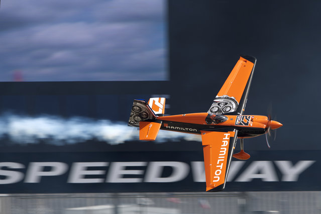 """Nicolas Ivanoff of France performs in front of the world's largest HD screen: the """"Big Hoss"""" during the finals for the sixth stage of the Red Bull Air Race World Championship at the Texas Motor Speedway in Fort Worth, Texas, United States on September 7, 2014. (Photo by Andreas Schaad/Red Bull)"""