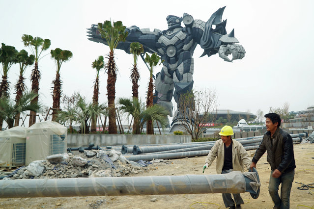 Construction workers carry a light pole in front of a giant robot statue in Guiyang, Guizhou province, China on November 24, 2017. In the push to become a center of innovative tech, Guizhou is luring firms such as Apple Inc, which has sited its China data center there, while the world's largest radio telescope is in nearby Pingtang county. (Photo by Joseph Campbell/Reuters)